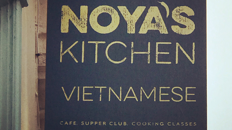 A blue sign, with gold text. The text reads: 'Noya's Kitchen - Vietnamese - Café / Supper Club / Cooking Classes'