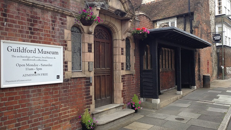 Front entrance to the Guildford Museum. A sign on the wall to left of the door reads: 'Guildford Museum. The archaeology of Surrey, local history and needlework collections. Open Monday - Saturday 11am-5pm. Admission Free.'
