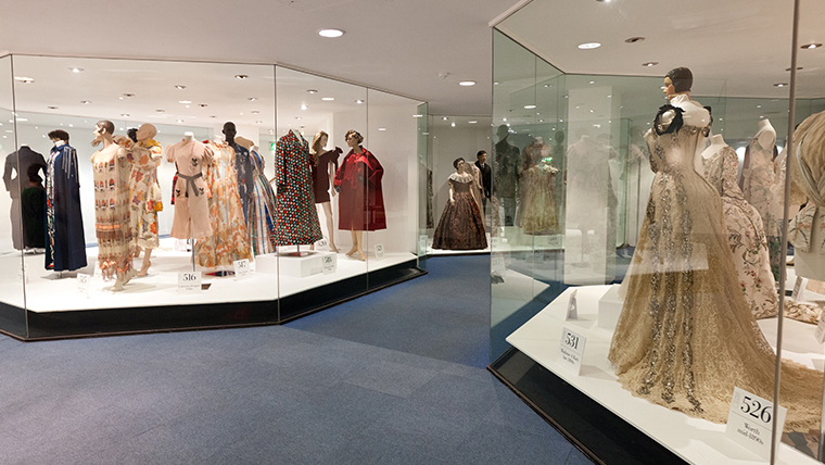 A view inside the Bath Fashion Museum. Exhibits in glass cases line both sides of a walkway.