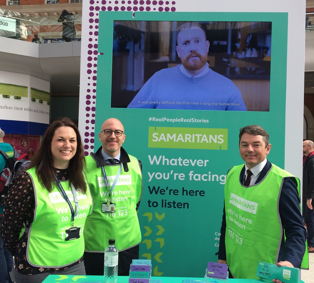 Three members of South Western Railway staff standing in front of a Samaritans banner