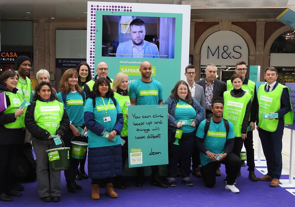 Group of Samaritans Volunteers and SWR staff standing in front of a Samaritans banner