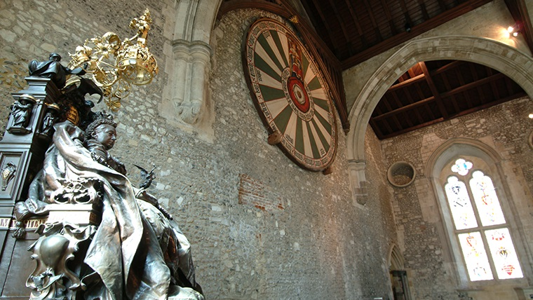 Body Image - a statue of Queen Victoria at the Great Hall, Winchester. The 'round table' from King Arthur's mythology hangs on the wall in the background.