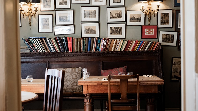 Body Image - The Wykeham Arms public house, interior. A row of books sits on a mantel, with chairs and tables in the foreground. The wall is covered with a number of hanging photos and images.