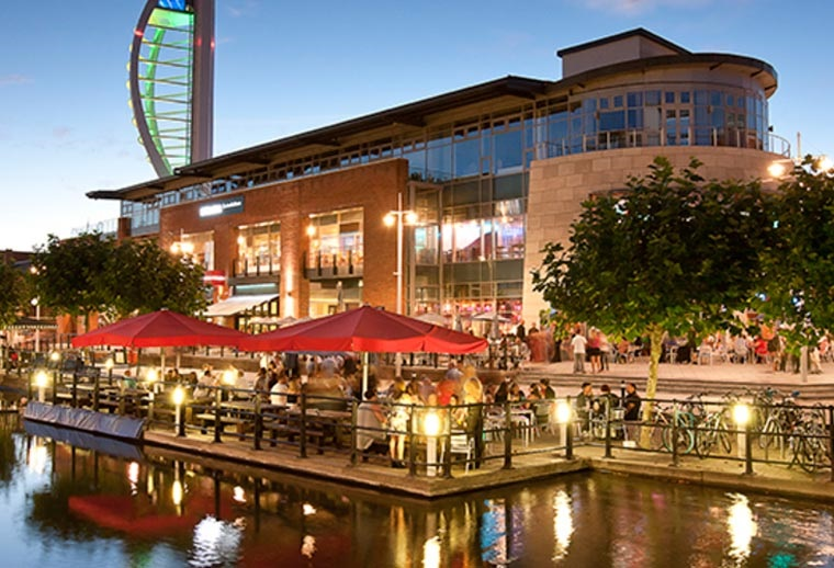 An outdoor shot of Gunwharf Quays at dusk. The image looks over the main eating area, and the Spinnaker Tower is in the background.