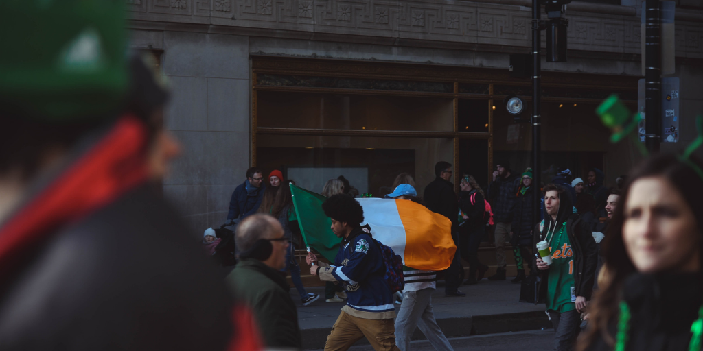 Scene on a street, a man carries an Irish flag while others around him wear St Patricks Day memorabilia