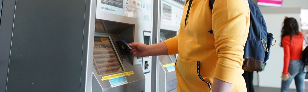 Man buying ticket from self-service machine