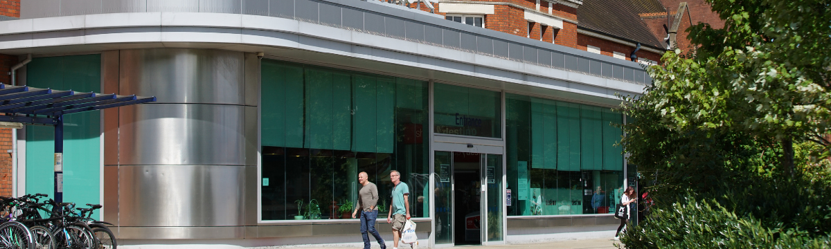 Front of Basingstoke station in summer. Two men are walking across the forecourt.